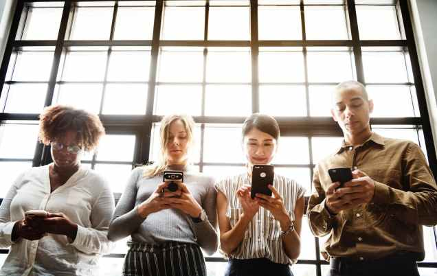 four people using smartphones behind glass wall